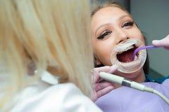 Dentisti femminili che curano paziente nella clinica fotografie stock