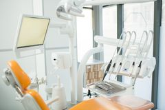 Dentistry clinics. Dentistry equipment and comfortable armchair for patients in contemporary dental clinics Royalty Free Stock Image