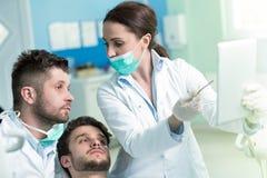 Dentistry education. Male dentist doctor teacher explaining treatment procedure. Stock Photography
