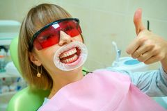 Dentistry happy patient in the chair in goggles royalty free stock photography