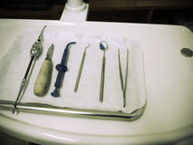 Dentistry instruments. Placed on a metal tray on white paper. Made of inox steel Royalty Free Stock Image
