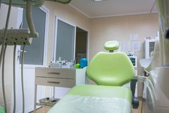 Professional dental unit with green chair and tools. Dentistry, medicine, medical equipment and stomatology concept royalty free stock image