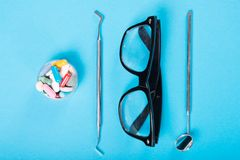 Dentistry set of tools glasses and cup of pills Royalty Free Stock Photo
