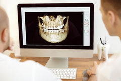 Dentists and assistant discussing the x-ray. Photograph on computer Stock Image