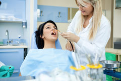 Dentists assisting a female patient Stock Photography