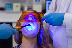 Dentists examining female patient with dental curing light Stock Images