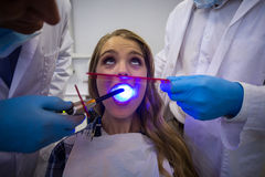 Dentists examining female patient with dental curing light Royalty Free Stock Image