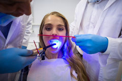 Dentists examining female patient with dental curing light Royalty Free Stock Photography