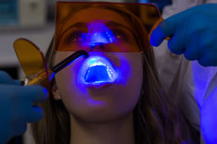 Dentists examining female patient with dental curing light Stock Photos