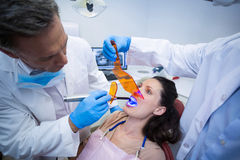 Dentists examining female patient with dental curing light Stock Photo