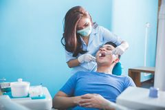 Dentists examining and working on young male patient stock photography