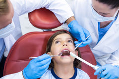 Dentists examining young patient in dental clinic Royalty Free Stock Photography