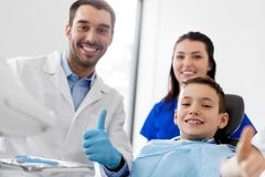 Dentists and happy kid patient at dental clinic. Medicine, dentistry and healthcare concept - dentists and happy kid patient at dental clinic showing thumbs up Royalty Free Stock Image