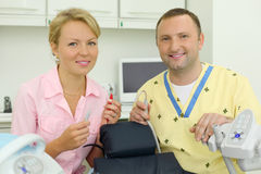 Dentists hold tools near chair for patient Stock Photo