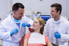 Dentists interacting with female patient Royalty Free Stock Image