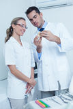Dentists looking at mouth model Stock Image