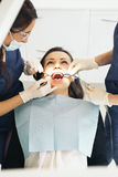 Dentists with a patient during a dental intervention Stock Photos
