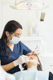 Dentists with a patient during a dental intervention. Stock Photos