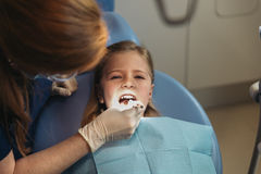 Dentists with a patient during a dental intervention to girl. Stock Photography