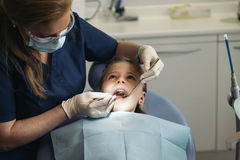 Dentists with a patient during a dental intervention to girl. Royalty Free Stock Photos