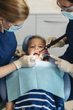 Dentists with a patient during a dental intervention to girl. Stock Image