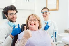 Dentists and patient in surgery being excited Royalty Free Stock Images
