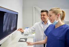Dentists with x-ray on monitor at dental clinic. People, medicine, stomatology, technology and health care concept - happy dentists looking to x-ray scan on stock image