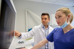 Dentists with x-ray on monitor at dental clinic. People, medicine, stomatology, technology and health care concept - dentists looking to x-ray scan on monitor at stock photo