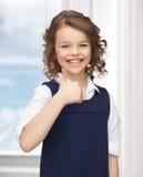 dentonåriga flickavisningen tummar upp Royaltyfria Foton