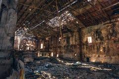 Dentro arruinada y abandonada construcción de viviendas espeluznante oscura de la fábrica, pasillo industrial del almacén fotografía de archivo