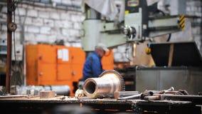Dentro da fábrica na tabela são as peças e as ferramentas de metal - no fundo, um homem trabalha em uma máquina-instrumento filme