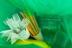 Dentro de la bolsa de plástico verde con los cubiertos y los paquetes no reutilizables fotografía de archivo