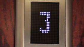 Dentro de levantar el elevador, el cierre para arriba de un indicador digital que muestra número y la flecha del piso en blanco C almacen de metraje de vídeo