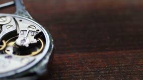 Dentro de mecanismo del reloj en un fondo de madera elegante metrajes