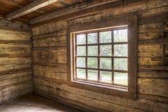 Dentro de uma casa velha do log que enfrenta janelas Imagem de Stock