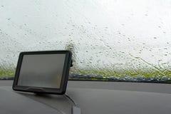 Dentro de un coche con lluvia en ventana y el sistema de navegación GPS del parabrisas en mún tiempo imagen de archivo libre de regalías