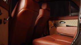 Dentro de un coche de lujo del vintage, asientos de cuero marrones, cámara en el movimiento metrajes