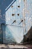 Dentro de un edificio industrial abandonado viejo, fábrica La pared con la peladura de la pintura azul Mucho diversa basura Unida Fotografía de archivo