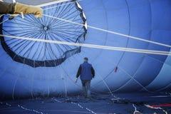 Dentro de un globo azul del aire caliente, el piloto anónimo comprueba las cuerdas fotografía de archivo