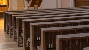 Dentro de una iglesia católica vacía Bancos de madera para los miembros de iglesia almacen de video