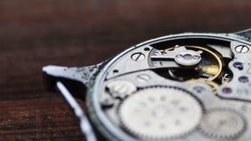 Dentro del meccanismo dell'orologio su un fondo di legno alla moda archivi video
