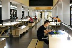 Dentro della biblioteca universitaria moderna, la gente che legge e che studia nel corridoio delle biblioteche Immagine Stock Libera da Diritti