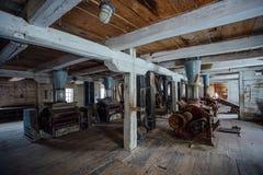 Dentro do moinho de madeira abandonado velho com equipamento velho Fotos de Stock