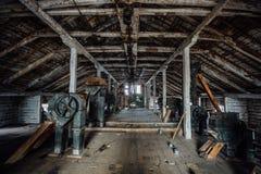 Dentro do moinho de madeira abandonado velho com equipamento velho Foto de Stock