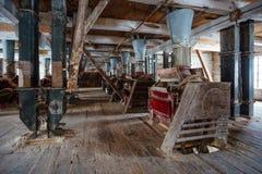 Dentro do moinho de madeira abandonado velho com equipamento velho Fotografia de Stock