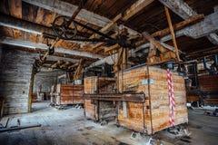 Dentro do moinho de madeira abandonado velho com equipamento velho Fotografia de Stock Royalty Free