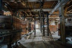 Dentro do moinho de madeira abandonado velho com equipamento velho Imagem de Stock