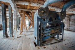 Dentro do moinho de madeira abandonado velho com equipamento velho Imagens de Stock
