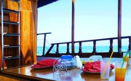 Dentro l'yacht sulla piattaforma in mare Tavola di legno con frutta e fotografia stock libera da diritti