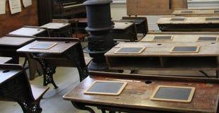 Dentro la vecchia aula di legno d'annata con il posto del fuoco nel mezzo fotografie stock libere da diritti